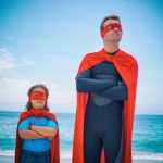 Confident man and son standing at sea shore